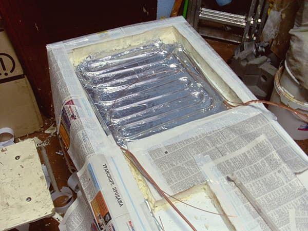 Вскрытие изоляции холодильного шкафа в мастерской для замены испарителя