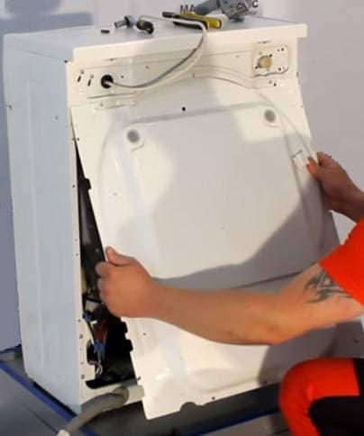 Снимаем заднюю стенку стиральной машины, чтобы получить доступ к помпе